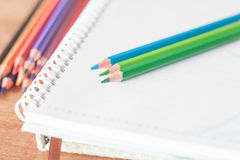 Closeup colorful pencils on spiral notebook and green notebook Royalty Free Stock Image