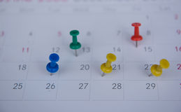 Closeup colorful pins push marking on a calendar. busy schedule Stock Photography