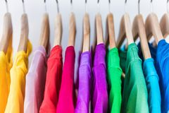 Closeup of colorful t-shirts on clothing rack. Fashion clothes on clothing rack - bright colorful closet. Closeup of rainbow color choice of trendy female wear stock images