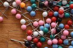 Closeup of colorful thumbtacks on a wooden table stock images