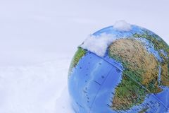 A closeup of colourful globe Earth covered in snow. A colourful globe Earth covered in snow, can be used as a concept for global warming stock image