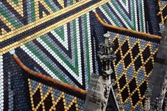 Closeup of colourful tiles and pinnacles on Stephansdom Vienna. Closeup of triangle pattern multi colored glazed tiles and carved pinnacles on the steep roof of Royalty Free Stock Photo