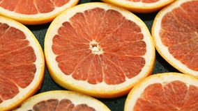 Composed slices of red grapefruit. Closeup of composed round slices of cut grapefruit of bright ret color arranged together on glass surface stock photography