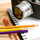 Closeup Composition with mechanic photocamera, pencils and a notebook Royalty Free Stock Images
