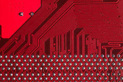 Closeup of computer circuit board in red. Macro shot of the backside of a computer circuit board or motherboard Royalty Free Stock Photos