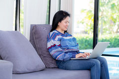 Closeup computer notebook on sofa with asian woman for work. Stock Image