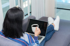 Closeup computer notebook on sofa with asian woman for work. Stock Photos