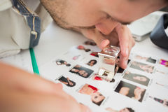 Closeup of a concentrate male artist looking at photos. In the office Royalty Free Stock Images