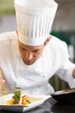 Closeup of a concentrated male chef garnishing food. In the kitchen stock image