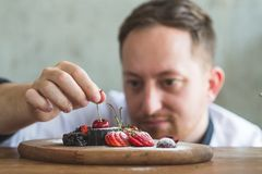 Closeup of a concentrated male pastry chef. Decorating dessert in the kitchen Stock Image