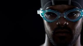 Closeup of concentrated male swimmer face in goggles, looking directly at camera. Stock photo Stock Image