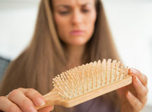 Closeup on concerned woman looking on hair comb Royalty Free Stock Images
