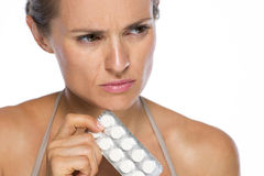 Closeup on concerned young woman with pack of pills. Isolated on white Royalty Free Stock Images