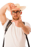 Closeup of confident happy traveler with straw hat framing photo. Graph with fingers over his face isolated Stock Images