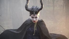 Closeup of a confused girl in the image of Maleficent in the misty forest