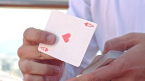 Closeup Conjurer Hands Shows Ace of Hearts Card Trick. Closeup european conjurer in white shirt shows ace of hearts trick out of card pack stock video footage