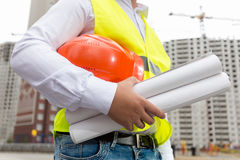 Closeup of construction engineer holding blueprints and orange h. Closeup image of construction engineer holding blueprints and orange hardhat at building site Royalty Free Stock Images