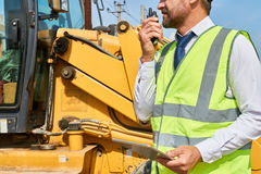 Construction Foreman Giving Instructions by Radio. Closeup of construction worker wearing suit and reflective jacket talking via portable radio set standing by royalty free stock images