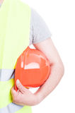 Closeup of constructor with vest holding his helmet. Closeup of constructor with vest holding his orange helmet isolated on white studio background Royalty Free Stock Images