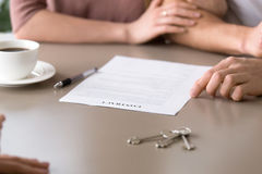 Closeup of contract on the table, couple taking mortgage loan. Close up photo of mortgage contract and keys on the table. Couple decided to take out mortgage for Royalty Free Stock Photo