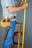 Contractor Standing on Ladder Measuring Stock Photography