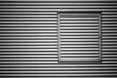 Corrugated iron facade with metal frame. The closeup of the corrugated iron facade of an industrial building with a metal window frame stock photo