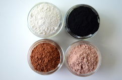 A closeup of cosmetic clays for detox face masks - French green clay, kaolin, pink clay, red clay and powdered activated charcoal Royalty Free Stock Image