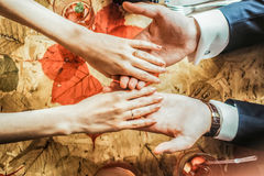 Closeup couple  hands holding each other at the restraunt. Closeup couple  hands with wedding  rings holding each other at the restraunt wooden table with Stock Images