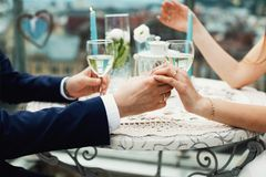 Closeup of couple hands on restaurant table with two glasses of. Champagne. Romantic couple holding each other`s hand at dinner in a luxury restaurant Stock Image
