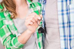 Closeup of couple holding key ring to their new house.  Royalty Free Stock Image