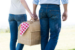 Closeup Of Couple Holding Picnic Basket. Young Couple Walking Holding Picnic Basket Together Stock Image