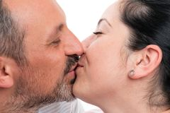 Closeup of couple kissing lips. Closeup of men and women couple kissing lips as romantic relationship concept isolated on white studio background stock photography