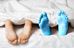 Closeup of a couple lying in bed barefeet.  Stock Photo