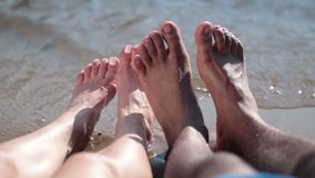 Closeup of couple's feet relaxing on the beach stock footage