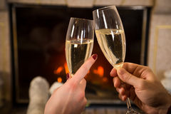 Closeup of couple`s hands with glass of champagne near fireplace Stock Photos