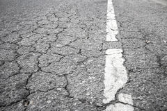 Closeup of cracked asphalt road Royalty Free Stock Photos