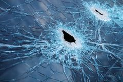 Closeup of Cracked Glass from Gunshot. Closeup of a whole and cracked windshield produced by gunshots Royalty Free Stock Photography