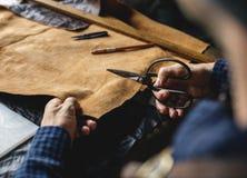 Closeup of craftsman cutting leather handicraft stock image