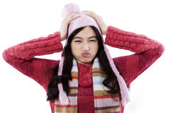 Closeup of cranky girl wearing sweater. Cranky expression of young girl wearing knitted clothes and hat, isolated on white background Stock Photography