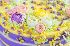 Closeup cream floral decoration on colorful cake Royalty Free Stock Image