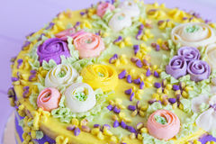 Closeup cream floral decoration on colorful cake Royalty Free Stock Images