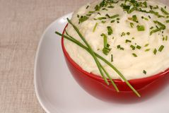Closeup of creamy mashed potatoes with chives in a red bowl Stock Photo