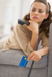 Closeup on credit card in hand of concerned woman with phone Royalty Free Stock Image