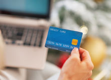 Closeup on credit card in hand of woman with laptop Royalty Free Stock Photography