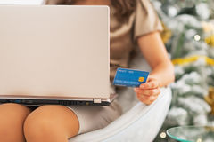 Closeup on credit card in hand of woman with laptop Stock Photos