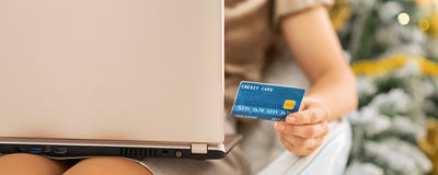 Closeup on credit card in hand of woman with laptop Stock Images