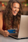 Closeup on credit card in hand of woman usign laptop in kitchen Royalty Free Stock Photos