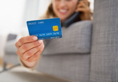 Closeup on credit card in hand of young woman talking phone Royalty Free Stock Photos