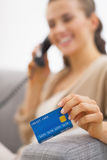 Closeup on credit card in hand of young woman talking phone Stock Image
