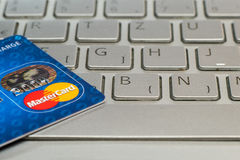 Closeup of credit card MasterCard. On laptop keyboard. Stock Photos